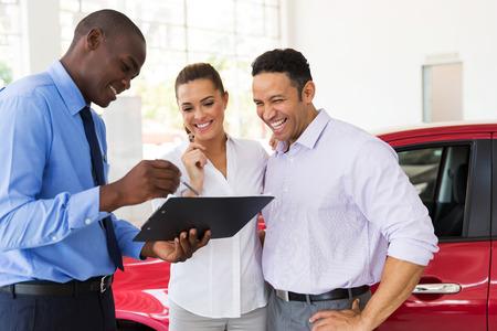 afrikanischer Autohändler, der Kaufvertrag Paaren erklärt, die ein Auto kaufen Standard-Bild