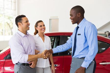 african american handshake: happy car salesman handshaking with middle aged buyer
