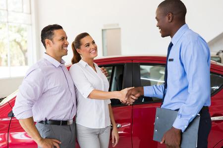 beau couple poignée de main avec le vendeur de voiture après l'achat d'une voiture Banque d'images