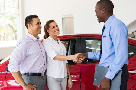 african american handshake: beautiful couple handshake with car salesman after purchasing a car