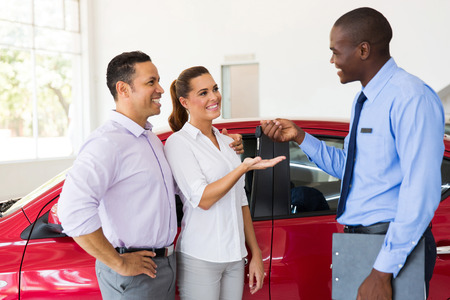 car salesman handing over new car key to couple in car showroom