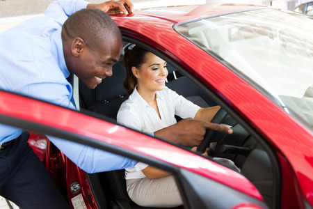 car sales: african salesman showing a new car to beautiful young woman