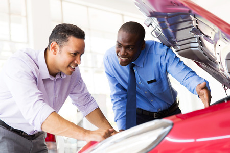 engine bonnet: happy sales consultant and customer looking at a car engine