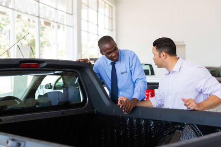 selling service smile: confident car salesman selling a car to middle aged customer