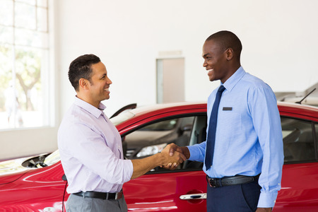 lachende african Amerikaanse auto dealer handdruk met de klant Stockfoto