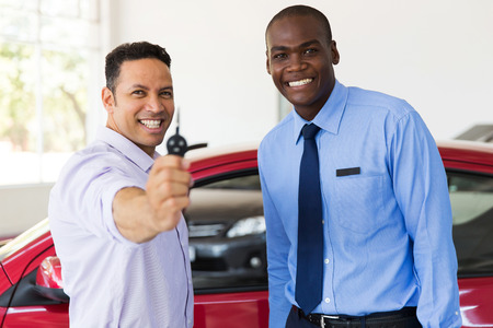 new age: mid age man showing new car key at dealership