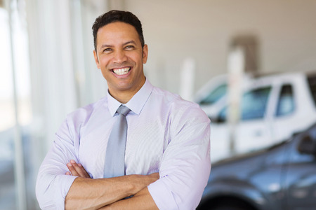 professional portrait: cheerful vehicle dealership principal with arms crossed in showroom