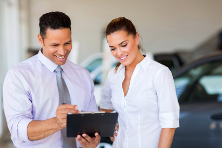auto sales: handsome vehicle dealership principal and saleswoman looking at clipboard Stock Photo