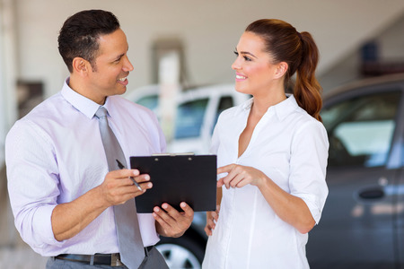 sales agent: two happy car sales consultants working inside vehicle showroom