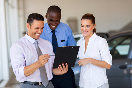 sales lady: group of happy car sales consultants working inside vehicle showroom