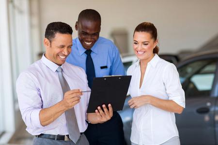 sales team: group of happy car sales consultants working inside vehicle showroom