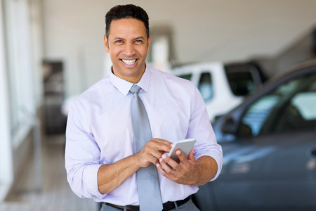 sales person: handsome middle aged man using smart phone at car dealership Stock Photo