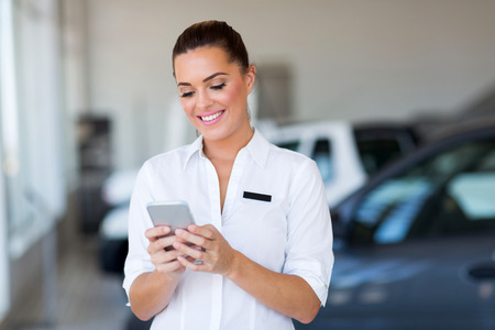 selling service: beautiful young car sales consultant using smart phone at showroom