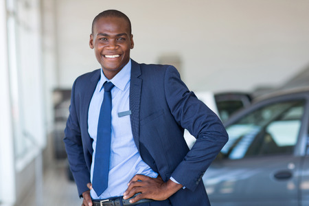 young african american car dealership principal standing in vehicle showroom