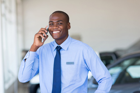 african american car salesman talking on cell phone in showroom Stock Photo