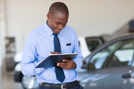 director de escuela: African American hombre exitoso que trabaja en sala de exposición de vehículos