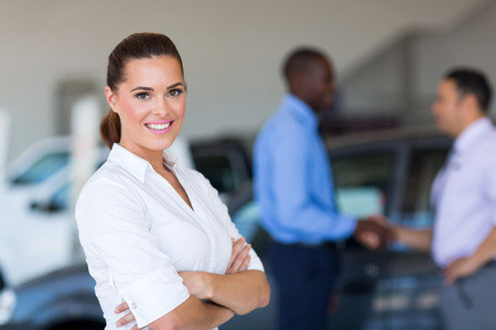 portrait of beautiful young saleswoman standing inside vehicle showroom