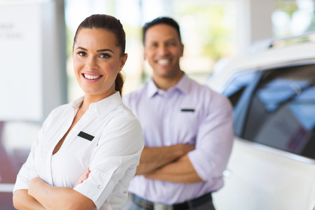 saleswoman: pretty young saleswoman with co-worker on background Stock Photo
