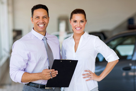 female worker: portrait of two workers standing inside car showroom Stock Photo
