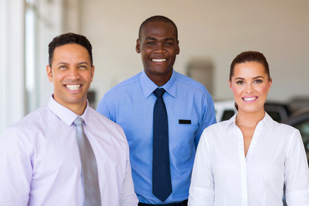 white work: group of car dealership staff standing in showroom Stock Photo
