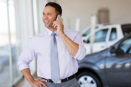 salesman: handsome car salesman talking on cell phone in showroom