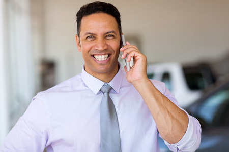 mid age: mid age man talking on smart phone at car dealership Stock Photo