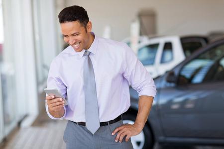 happy car salesman using smart phone in showroom Standard-Bild