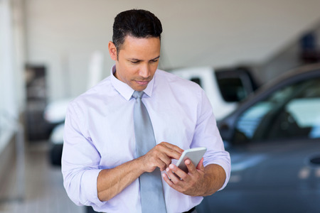 text: mid age car salesman using cell phone in showroom
