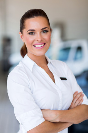 selling service smile: beautiful saleswoman standing at car dealership