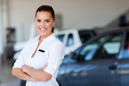 pretty female car dealer with arms crossed Standard-Bild