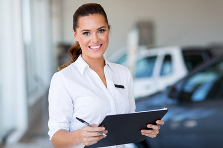 young car saleswoman holding clipboard in showroom