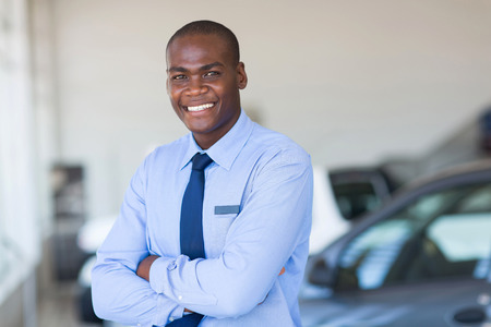 portrait de heureux vendeur de voitures africain en showroom