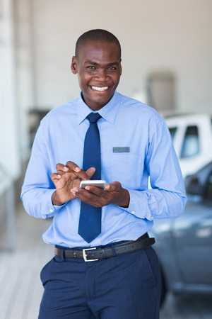 telephone salesman: cheerful young african car salesman using smart phone