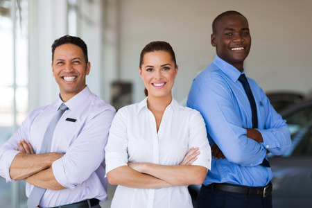 ethnic people: vehicle sales team with arms crossed inside car showroom Stock Photo