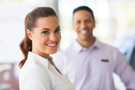 car sales: attractive vehicle sales woman standing in front of colleague Stock Photo