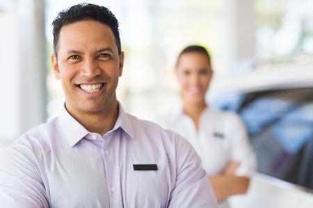 salesman: car salesman standing in front of colleague in showroom