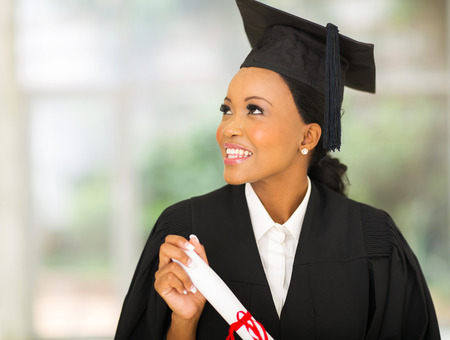 beautiful young african college graduate looking up photo