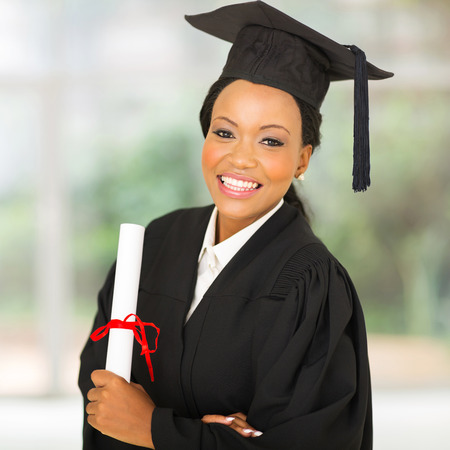 graduation cap and diploma: gorgeous female african university graduate looking at the camera