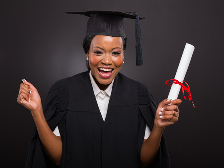 excited african university student holding her graduation certificate photo