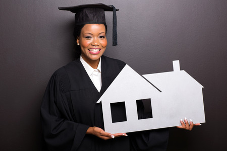 home school: african american graduate holding home symbol isolated on black background
