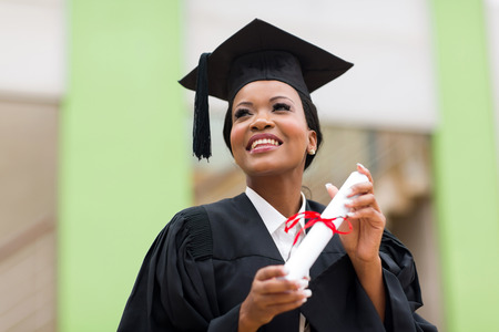 pretty african college student in graduation cap and gown in front of school building