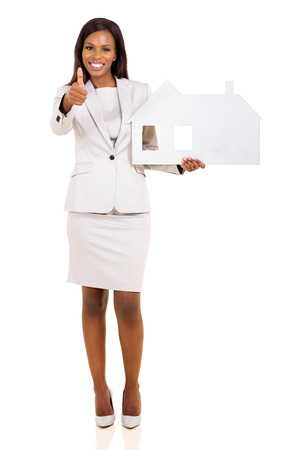 pretty afro american woman holding paper house and giving thumb up photo