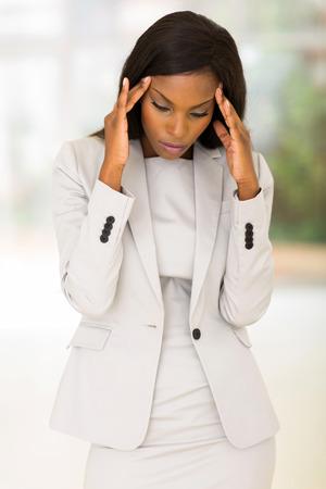 mujeres tristes: triste afroamericana empresaria tiene dolor de cabeza en el trabajo