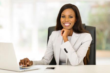 アフロアメリカン: オフィスで働くアフロ アメリカ人実業家の笑みを浮かべてください。