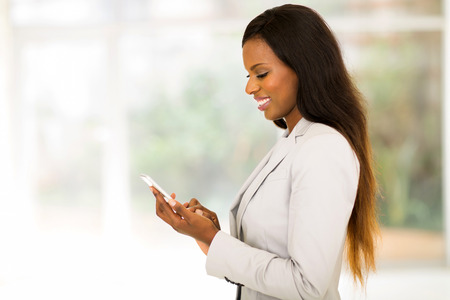 to the secretary: side view of happy african secretary using smart phone Stock Photo