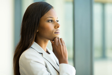 charming business lady: thoughtful african businesswoman in modern office Stock Photo