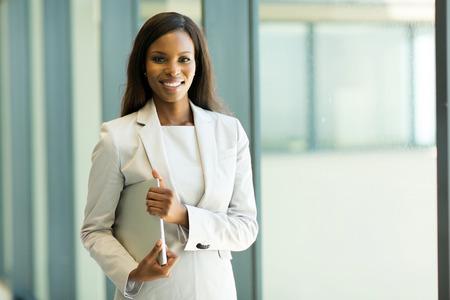 femmes souriantes: jolie jeune africain ordinateur portable employé de bureau tenant Banque d'images