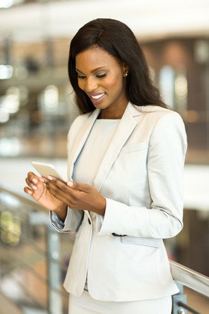 lady on phone: successful african american businesswoman using smart phone in modern office Stock Photo