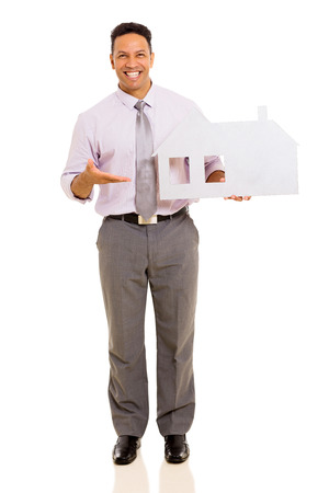 happy middle aged man presenting white paper house on white background photo