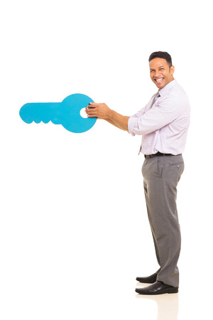 side keys: side view of happy middle aged man opening with a huge key isolated on white